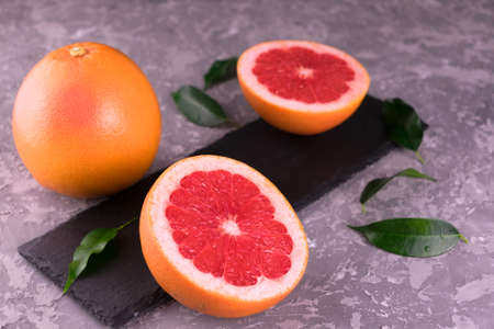 Grapefruit and grapefruit wedges on a gray background. Close-up.