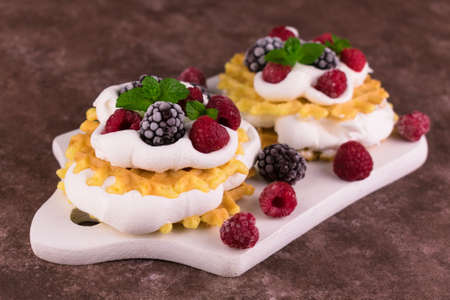 Waffles with airy protein cream and fresh berries on a brown background.