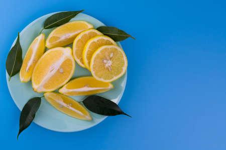 Sliced lemons on a blue plate on a light blue background.Flat lei.Copy space