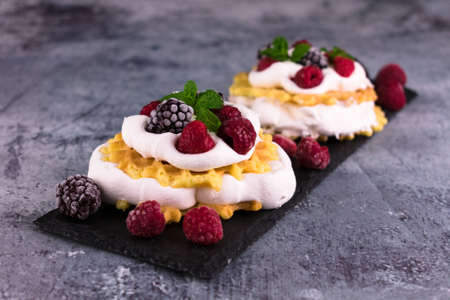 Waffles with delicate cream and berries on a black slate board. Stock fotó