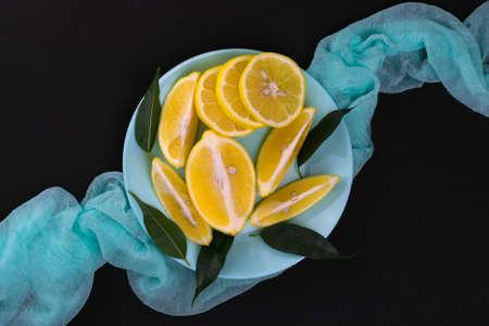 Sliced lemons on a blue plate on a black background. Flat lei.