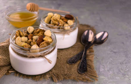 Greek yogurt with honey and nuts on  gray
