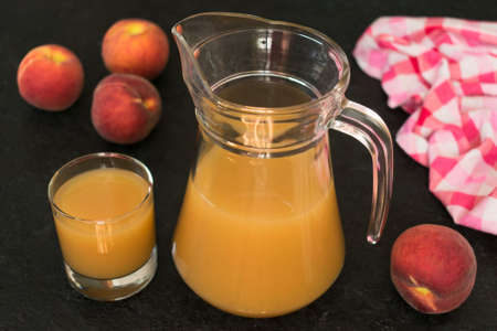 Peach juice in a jug and ripe peaches on a black background. Stock fotó