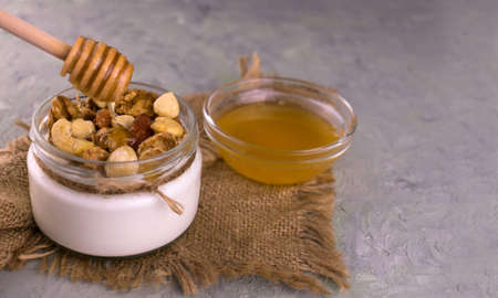 Greek yogurt with honey and different nuts on  gray