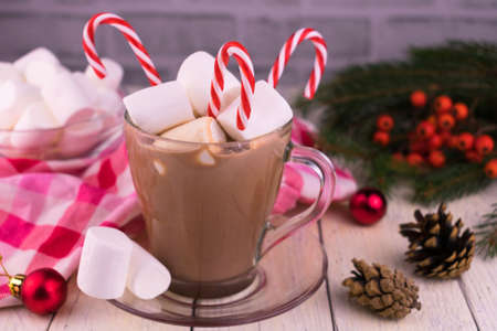Cup with Christmas cocoa with marshmallows on the background of Christmas decorations.