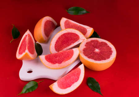 Sliced grapefruit on a white wooden board on a red background. Stock fotó