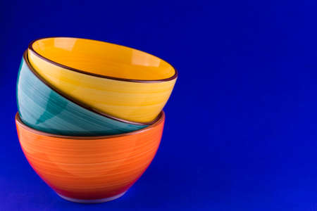 Bright ceramic bowls on a blue background.Copy space.