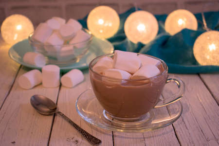 A cup of cocoa with marshmallows on a white wooden table against the background of Christmas lights.