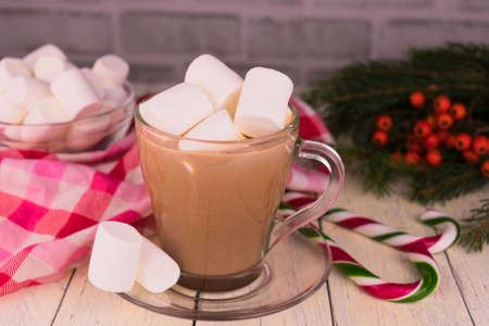 Cup of Christmas cocoa with marshmallows and lollipops on the background of Christmas decorations.