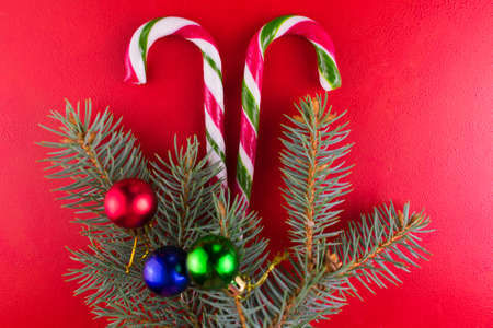 Christmas composition of striped candies and a Christmas tree on a red background. Stock fotó
