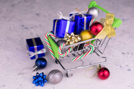 Small shopping cart with gift and branches of a Christmas tree with decoration on a white background. Concept for Christmas and New Years sales. Stock fotó