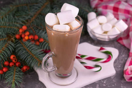 Cocoa with marshmallows in a tall glass on the background of Christmas decorations. Stock fotó