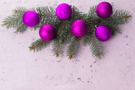 Christmas tree decorated with large lilac balls on a white textured background. Copy space.
