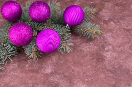 Branches of a Christmas tree decorated with purple balls on a gray textured background. Copy space. Stock fotó