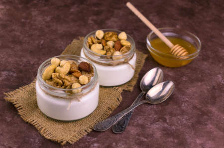 Greek yogurt in small jars with nuts and honey on a brown background. Stock fotó