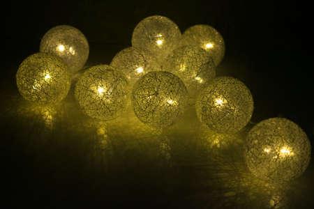 Yellow lanterns burn in the dark. Shining Christmas balls.