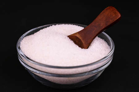 Sugar in a glass bowl and a wooden spoon on a black background. Close-up.