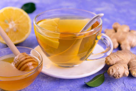 A cup of tea with ginger honey and lemon on a light blue background. Close-up.
