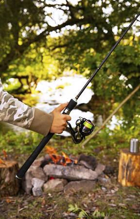 A fisherman with a fishing rod. Close-up of a hand holding a spinning rod and twisting a coil. Colorful view, blurred background, selective focus. Stock Photo
