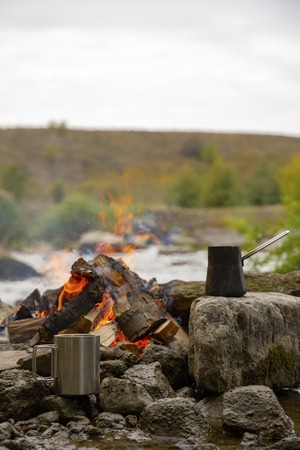 Aromatic and hot coffee on the fire. Bonfire and thermo mugs. Bonfire on the river bank.