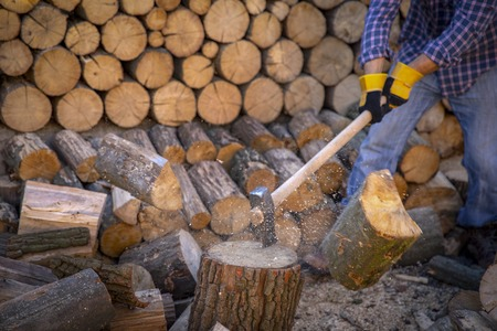 Man holding an industrial ax. Ax in hand. A chain of chains and firewood. Strong man lumberjack with an ax in his hand. Chainsaw close up.