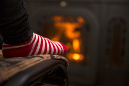 Feet in Christmas socks by the fireplace. Imagens