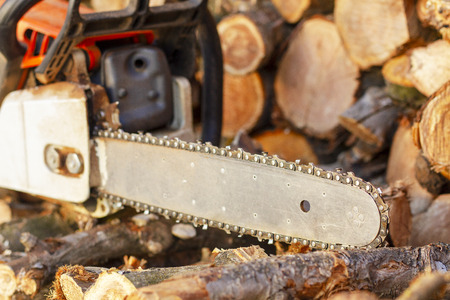 Chainsaw. Chainsaw close up. Chainsaw on the background of firewood.