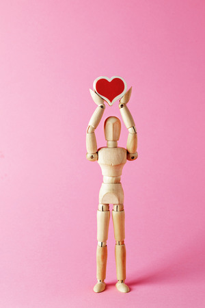 The mannequin is holding a heart. Wooden mannequin holds heart in his hands. Wooden mannequin. Wooden man.