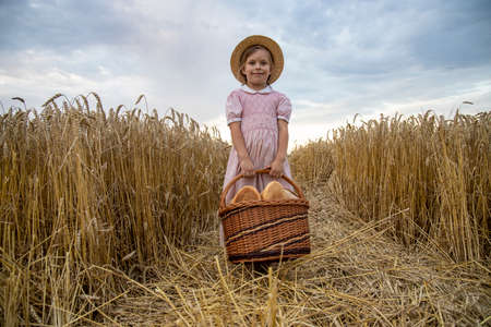 Little girl holding round bread. Hands holding big bread. Bakery products in a basket on a wheat field.