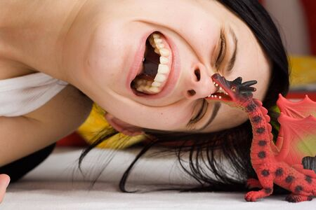attacked: portrait of a girl attacked by the dragon toy Stock Photo