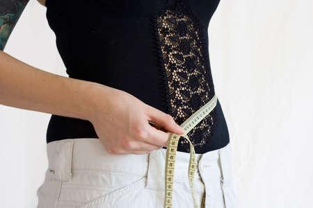 woman measuring her waist. loosing weight