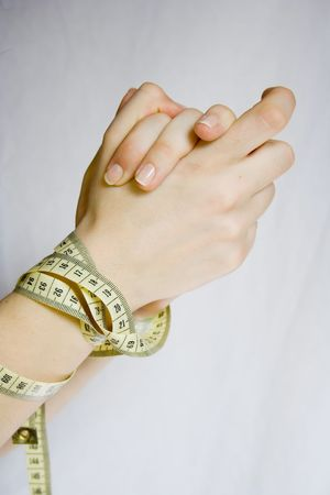 hands tied up with measure tape. diet issue Stock Photo