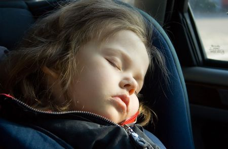 portrait of little girl sleeping in the car photo