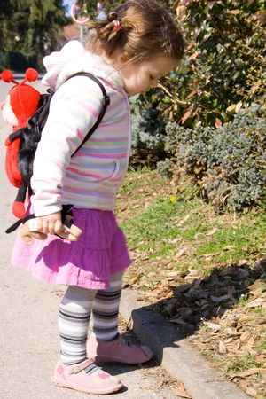 little girl with small backpack in the sun photo