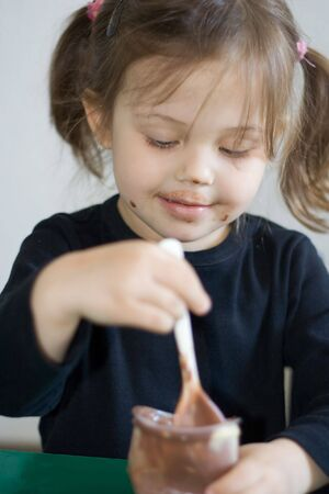 little girl eating her chocolate pudding Stock Photo - 895012