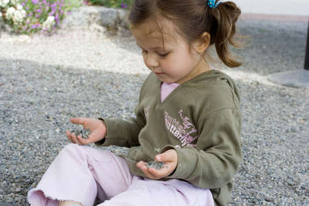 little girl playing with stones