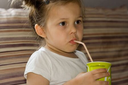 photo of little, cute girl drinking from a mug