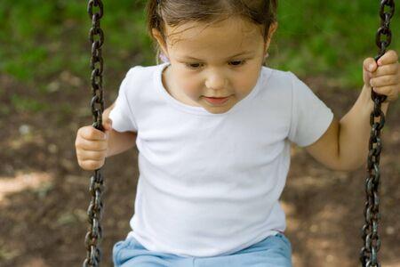 portrait of little girl on the swing photo