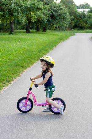 little girl riding on her pink bike Stock Photo