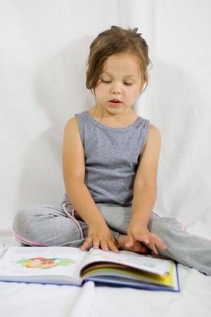 Little cute girl having fun while reading a book