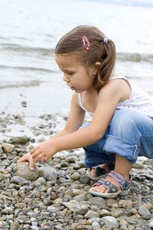 little cute girl playing at the beach.  photo
