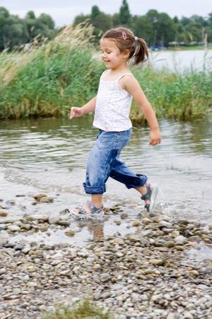 Niedliche kleine Mädchen spielt am Strand.  Lizenzfreie Bilder - 1423919