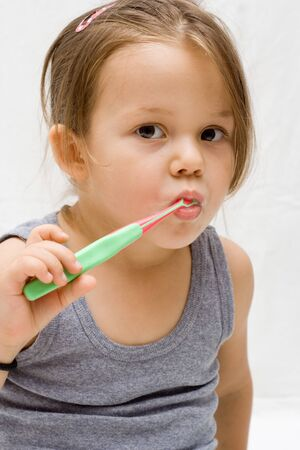 the little cute girl brushing her teeth