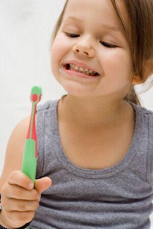 the little cute girl brushing her teeth