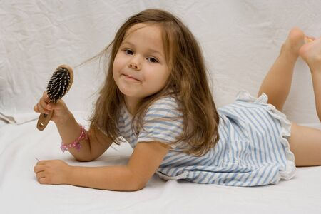 little girl barefoot: the little cute girl brushing her hair