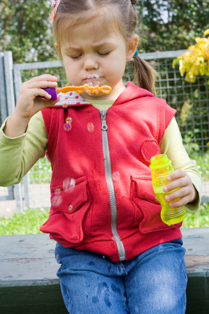 little girl having fun with making soap bubbles photo