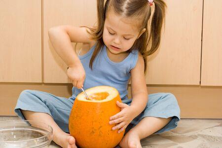 little, cute girl making a halloween lantern