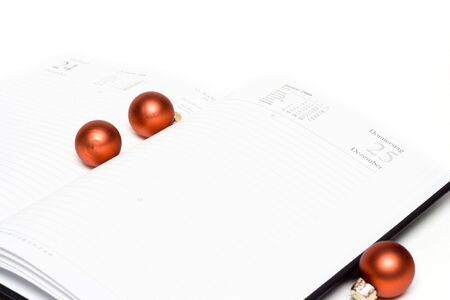 open calendar with glass balls isolated on white photo