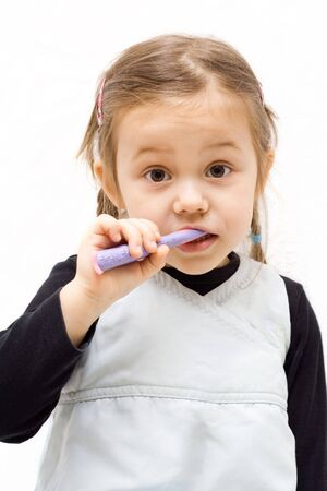 the little cute girl brushing her teeth photo