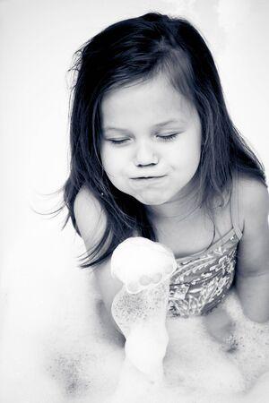 Little girl wearing swimsuit playing i the bathtube photo